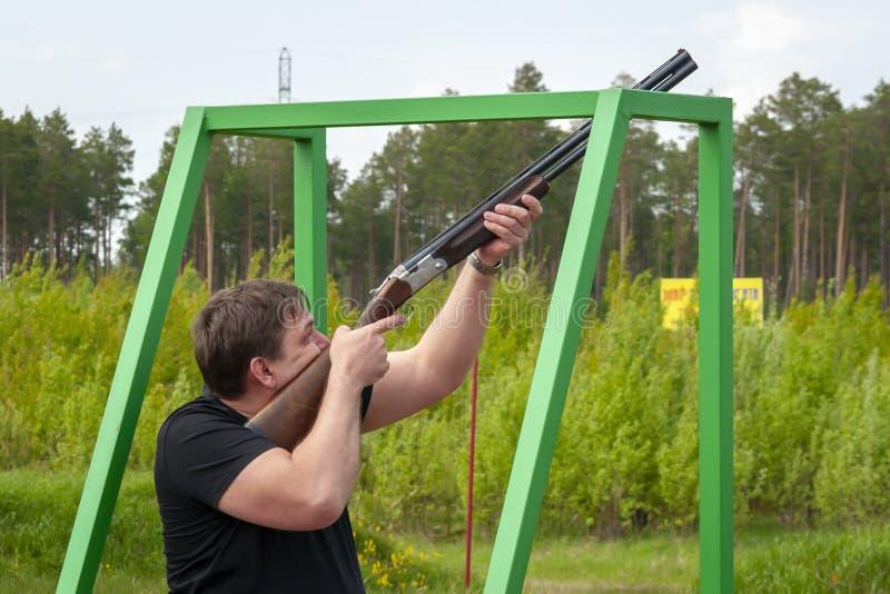 Een mens met een sportengeweer bij de het schieten waaier stock foto