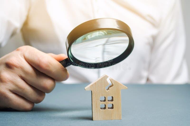 Een mens met een vergrootglas bekijkt een huis met een barst Het huis en de verzekeringsrisico's van de schadebeoordeling stock foto