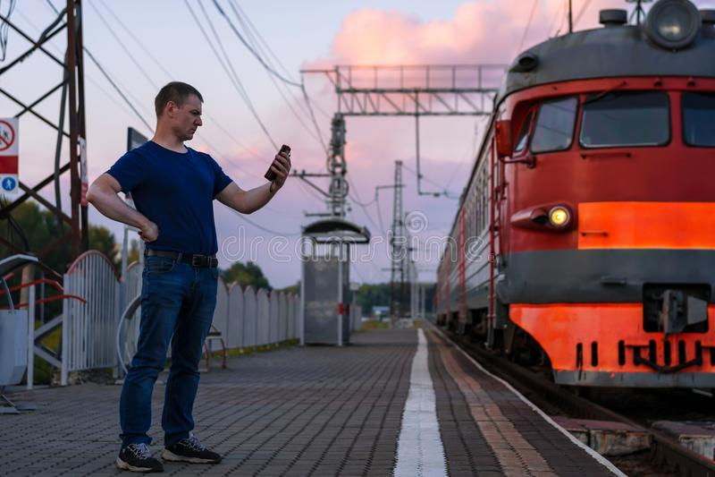 Een mens met vitiligo bij het station met een telefoon naast de trein royalty-vrije stock foto's