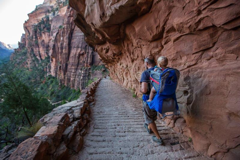 Een mens met zijn babyjongen is trekking in het nationale park van Zion, Utah, de V.S. royalty-vrije stock afbeelding