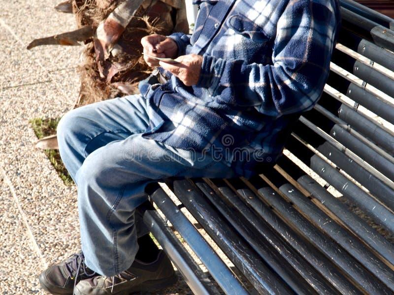 Een mens met zijn handige zitting op een bank stock fotografie