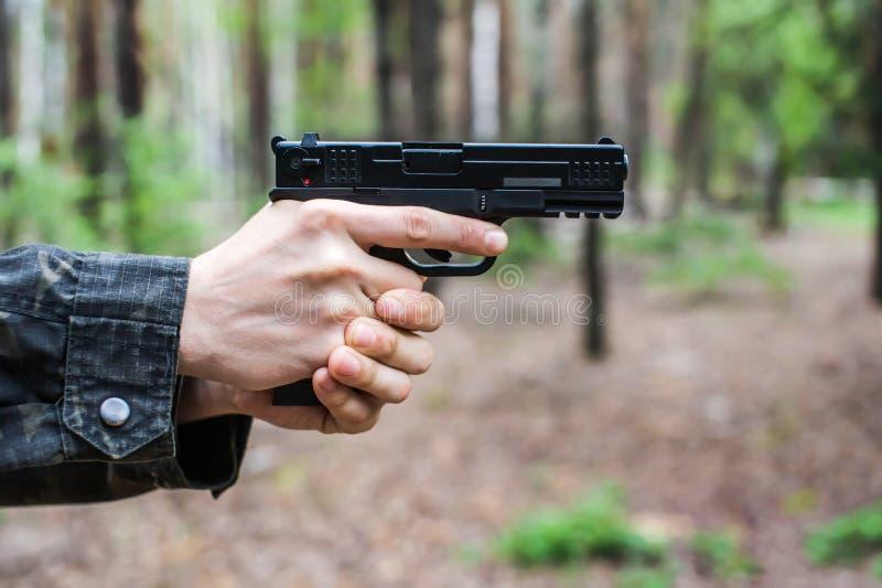 Een mens in militaire kleding streeft een pistool stock foto's