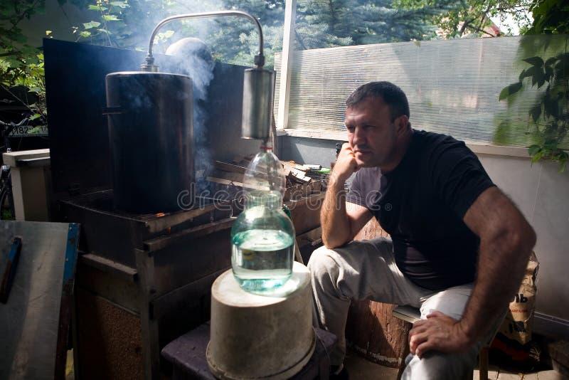 Een mens neemt waar hoe de maneschijn in een glaskruik stroomt royalty-vrije stock afbeeldingen