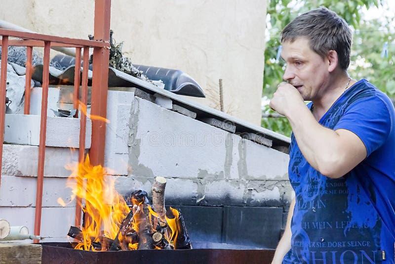 Een mens ontsteekt een brand in de koperslager royalty-vrije stock afbeeldingen