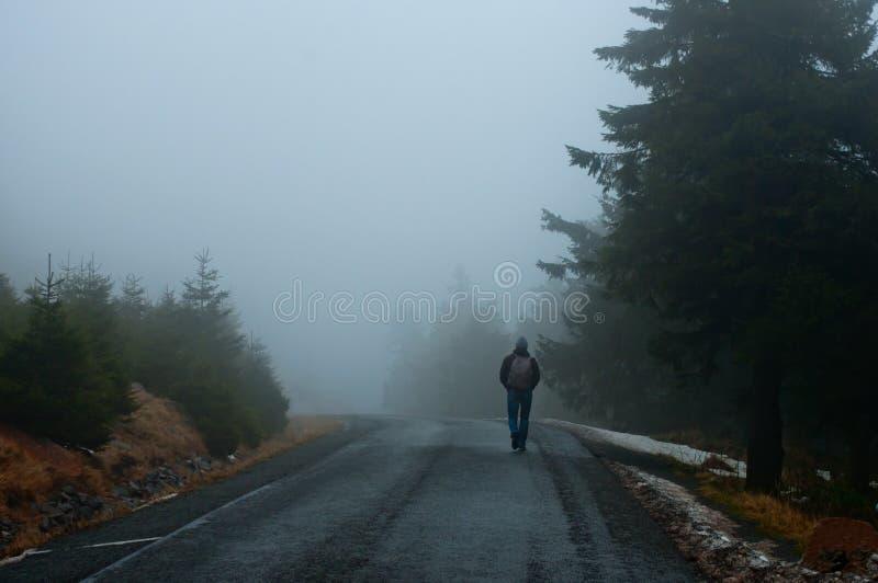 Een mens op een weg die in mist beëindigen stock fotografie