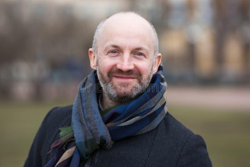 Een mens op middelbare leeftijd in een sjaal en jasje voor een gang royalty-vrije stock fotografie