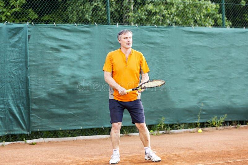 Een mens op middelbare leeftijd speelt tennis op een hof met een natuurlijk aardoppervlak op een zonnige de zomerdag royalty-vrije stock afbeeldingen
