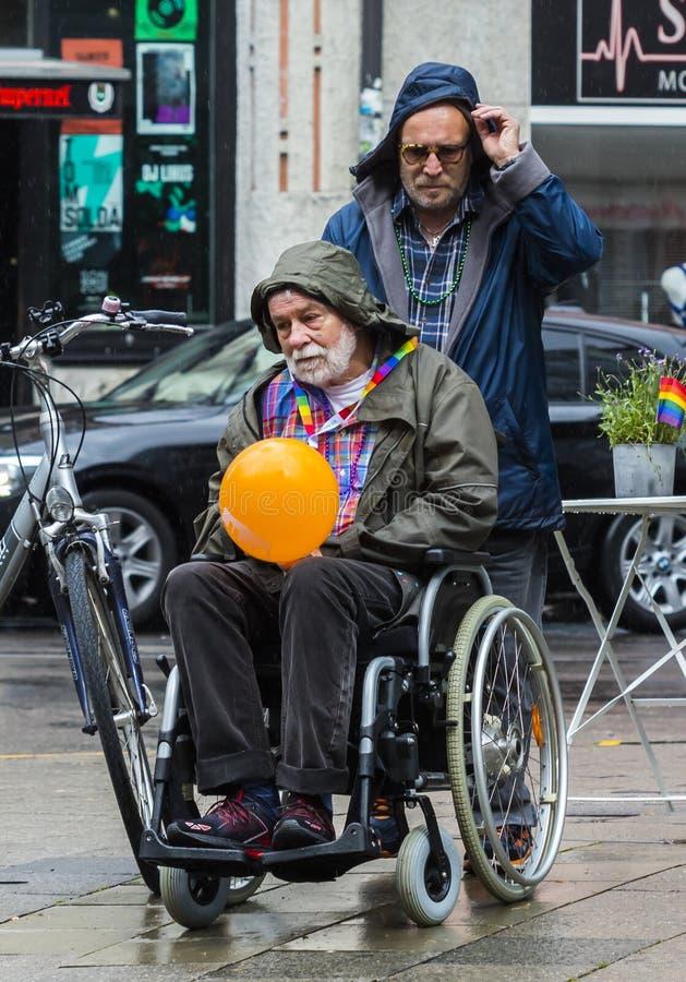 Een mens op een rolstoel met een vriend bij Christopher Street Day-CDD in München, Duitsland royalty-vrije stock fotografie