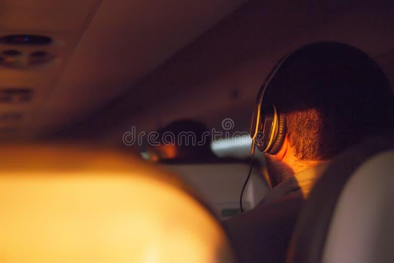 Een mens op een vliegtuig die aan muziek en het rusten luisteren royalty-vrije stock afbeelding