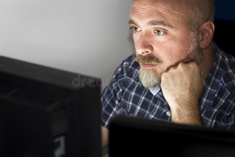 Een mens op zijn computer. stock afbeelding