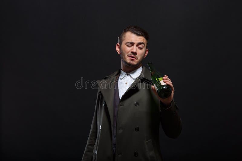 Een mens op een zwarte achtergrond houdt een fles in zijn hand, onderzoekt de fles, achter het oor een sigaret stock afbeeldingen
