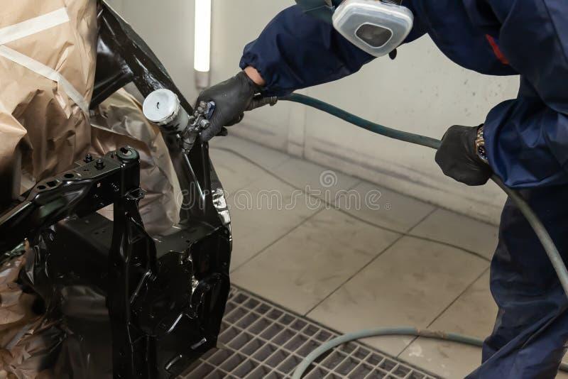 Een mens in overall en de zwarte handschoenen bespuiten zwarte verf op een autokader tijdens een lichaamsreparatie in de autodien royalty-vrije stock foto