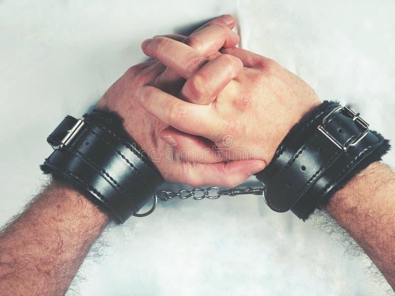 Een mens overhandigt het dragen van zwarte bont het stuk speelgoed van het leergeslacht handcuffs stock afbeeldingen