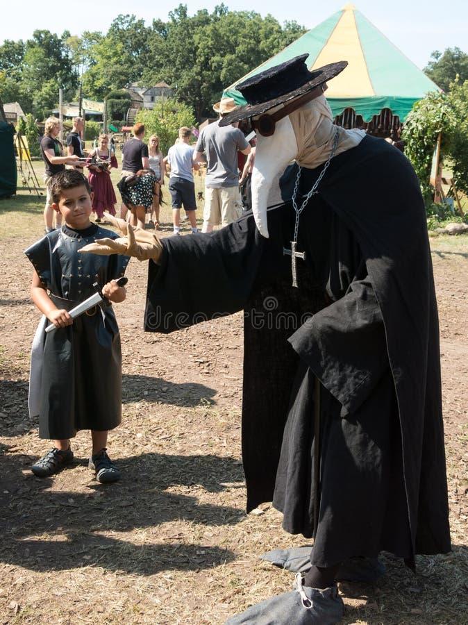 Een mens in plaag artsenkostuum en een jongen bij Renaissancefestival royalty-vrije stock foto