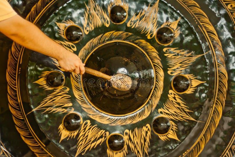 Een mens raakte grote gong stock afbeeldingen