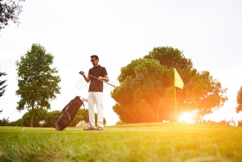 Een mens is rijk en zeker in modieus polo besteedt tijd speelgolf De professionele golfspeler wrijft een stok vóór effect stock fotografie