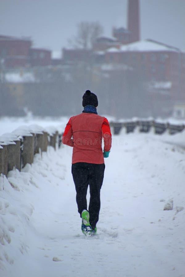 Een mens in een rood jasje die langs de dijk van de de winterstad tijdens een sneeuwval lopen stock afbeelding