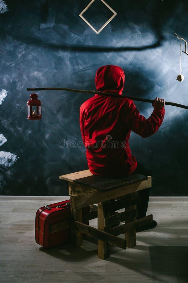 Een mens in een rood jasje op een zwarte achtergrond houdt een kaarslicht op een stok stock foto's