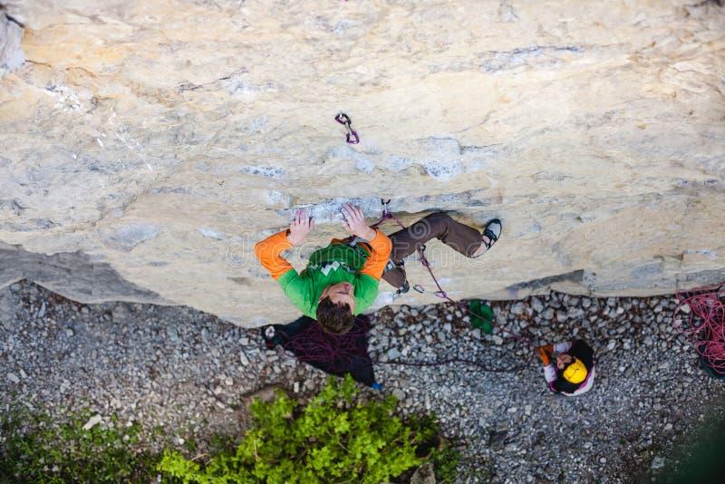 Een mens is een rotsklimmer op een rots stock afbeeldingen