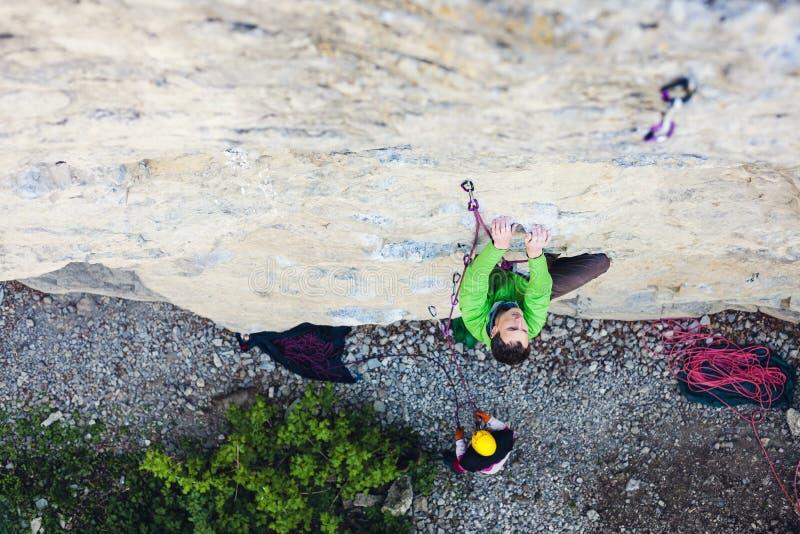 Een mens is een rotsklimmer op een rots stock afbeelding