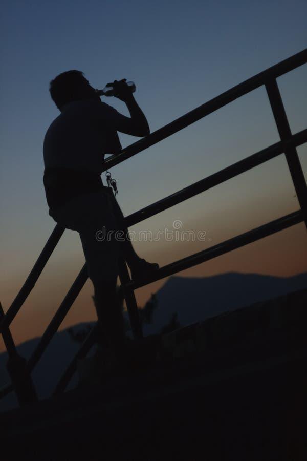 Een mens rust en drinkt water van een fles stock foto's