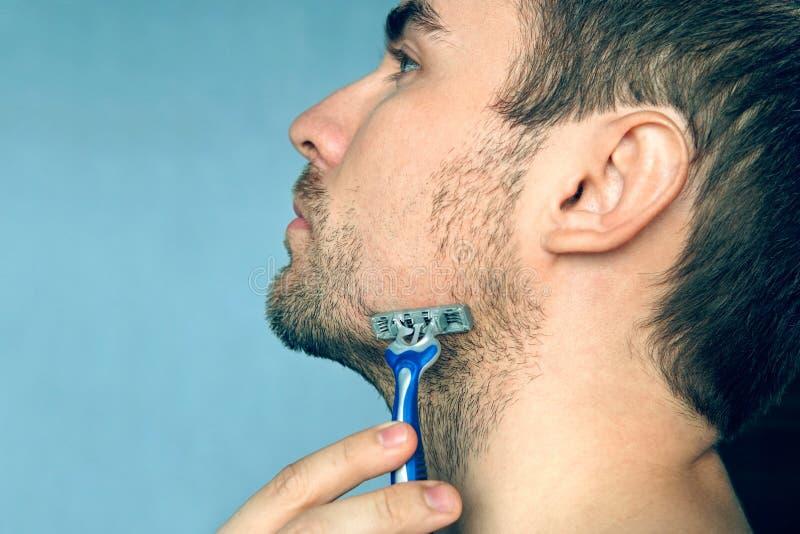 Een mens scheert een het scheren machine zonder schuim, zeep en crea te gebruiken royalty-vrije stock foto