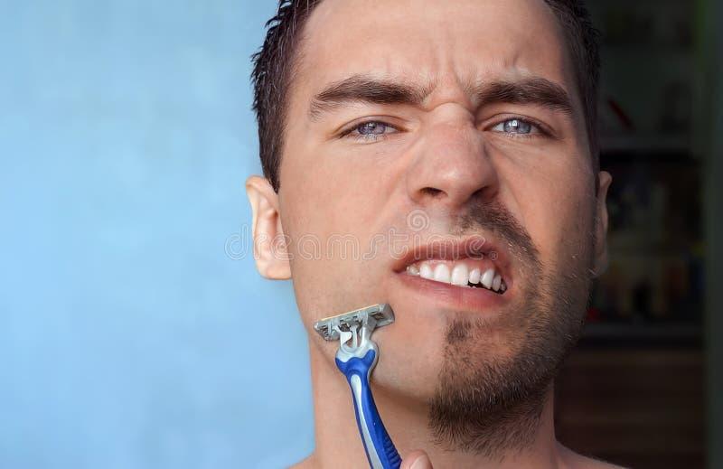 Een mens scheert zijn gezicht zonder room of schuim, ervarend pijn a royalty-vrije stock foto