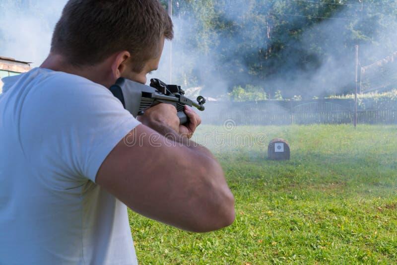 Een mens schiet een doel van een pneumatisch kanon Achtermening van een Mens royalty-vrije stock fotografie
