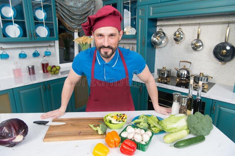 Een Mens in schort in de keuken die salade voor veganisten doen Knappe mens die thuis het voorbereiden van salade in keuken kookt stock foto's