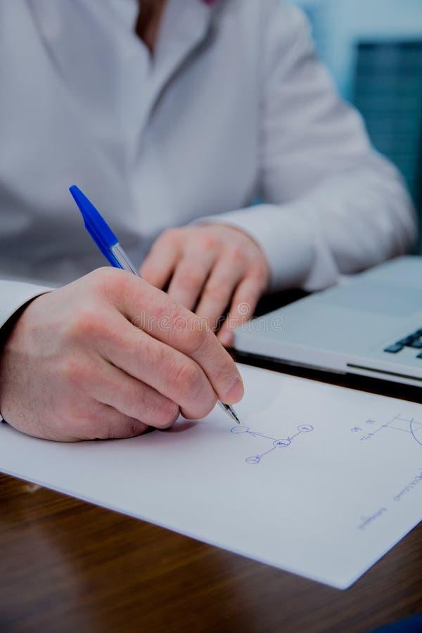 Een mens schrijft met een pen op een blad van document, zichtbare computer royalty-vrije stock afbeeldingen