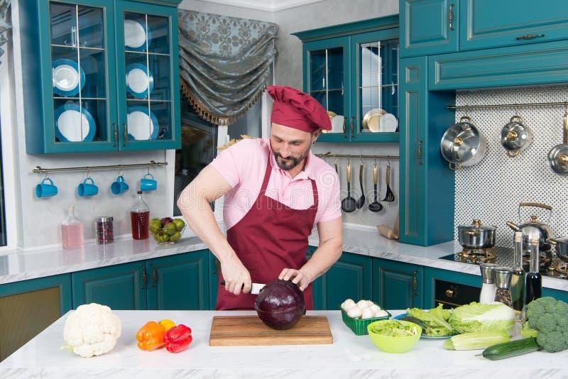 Een Mens sneed rode kool met wit mes De knappe chef-kok sneed rode kool Rode die kool door mes wordt gesneden De mensen houden va stock afbeelding