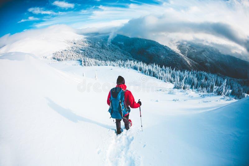 Een mens in sneeuwschoenen in de bergen in de winter royalty-vrije stock afbeelding