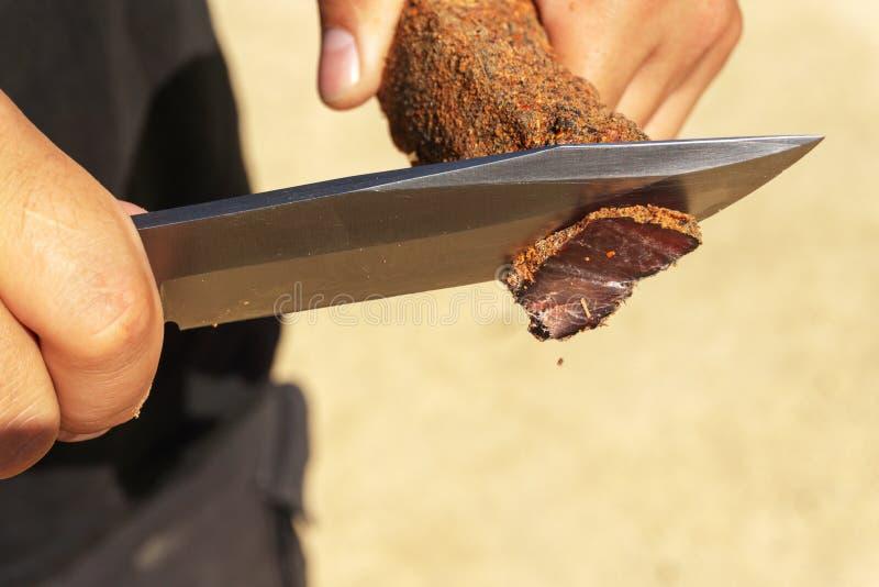 Een mens snijdt een basturma met een groot mes Close-up stock afbeeldingen
