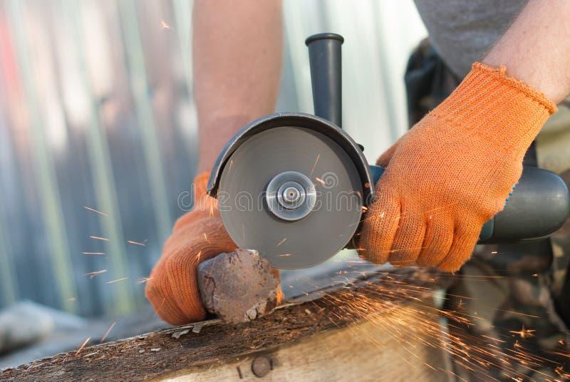 Een mens snijdt metaal stock afbeeldingen