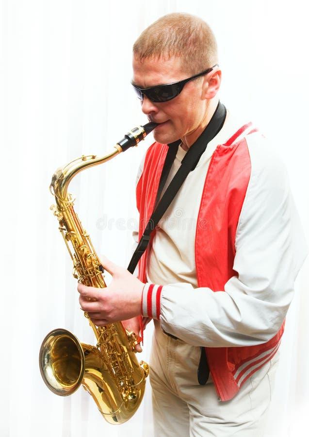 Een mens speelt de saxofoon royalty-vrije stock afbeeldingen