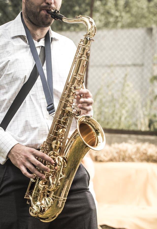 Een mens speelt de saxofoon stock afbeeldingen