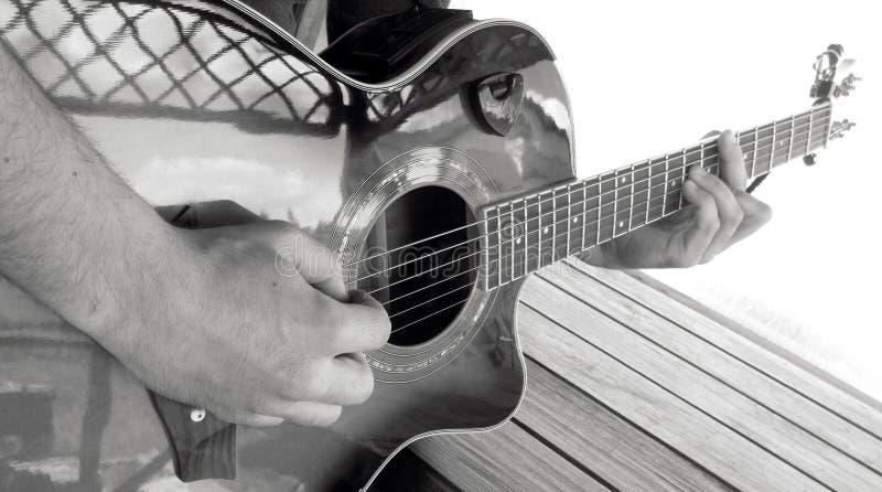Een mens speelt een akoestische gitaar met het beeld B van het twee handenclose-up royalty-vrije stock fotografie