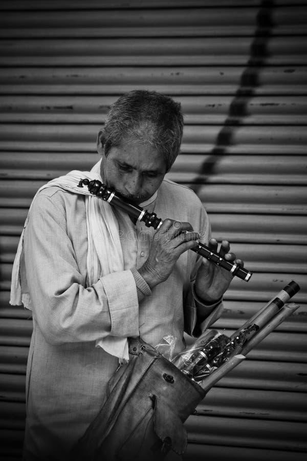 Een mens speelt een fluit klaar om op de straten van Katmandu, Nepal te verkopen royalty-vrije stock fotografie