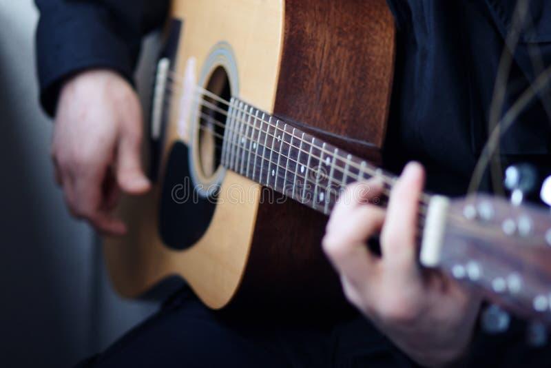 Een mens speelt een modieuze houten akoestische gitaar royalty-vrije stock foto