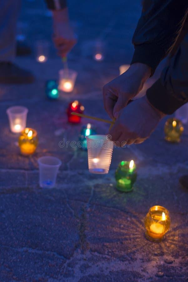 Een mens steekt een kaars aan Dag van Herinnering voor de Getroffenen stock afbeeldingen