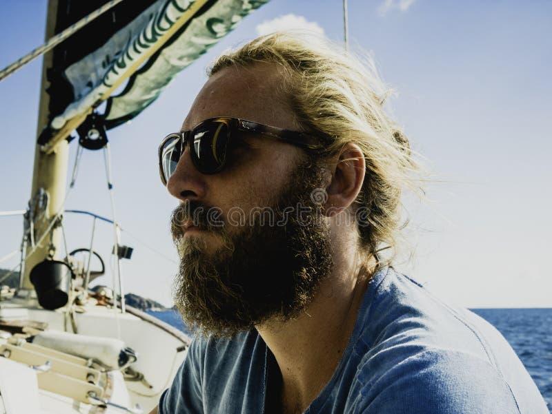 Een mens stuurt een zeilboot op een donkere dag in Golf van Thailand, Koh Tao, Thailand, Februari 2019 royalty-vrije stock foto