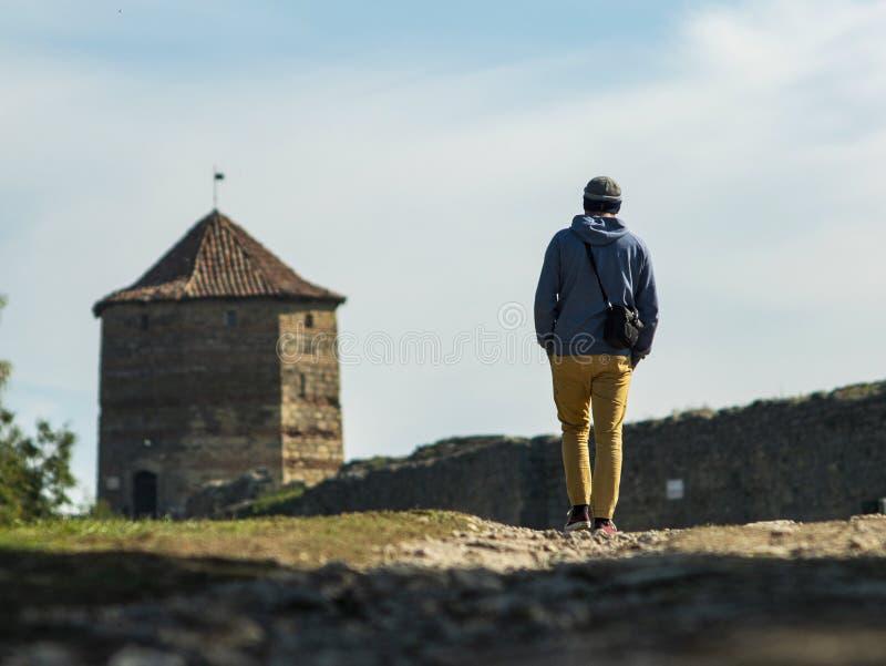 Een mens in een sweater met een kap en een gebreide hoed loopt langs de weg aan de vesting tegen de achtergrond van de toren en stock foto's