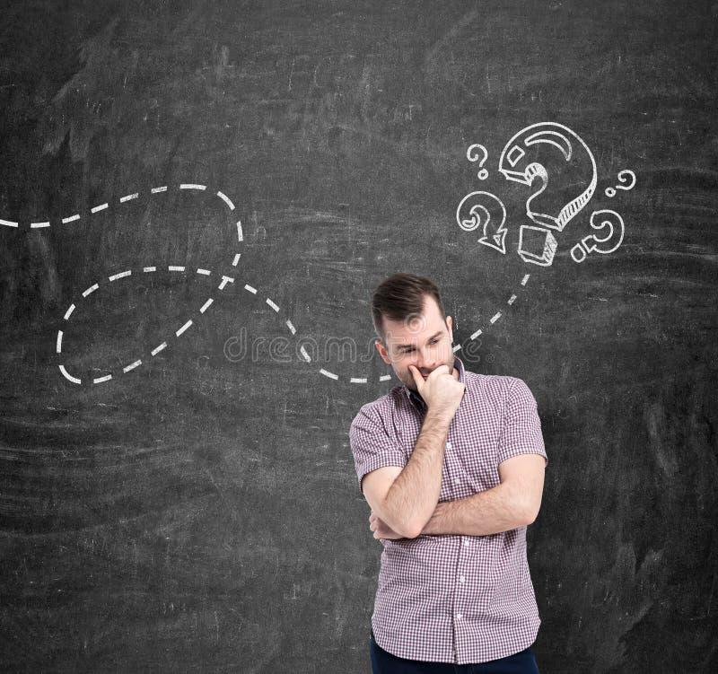 Een mens in toevallig overhemd denkt over onbeantwoorde vragen De vraagtekens worden getrokken op het zwarte bord royalty-vrije stock afbeelding