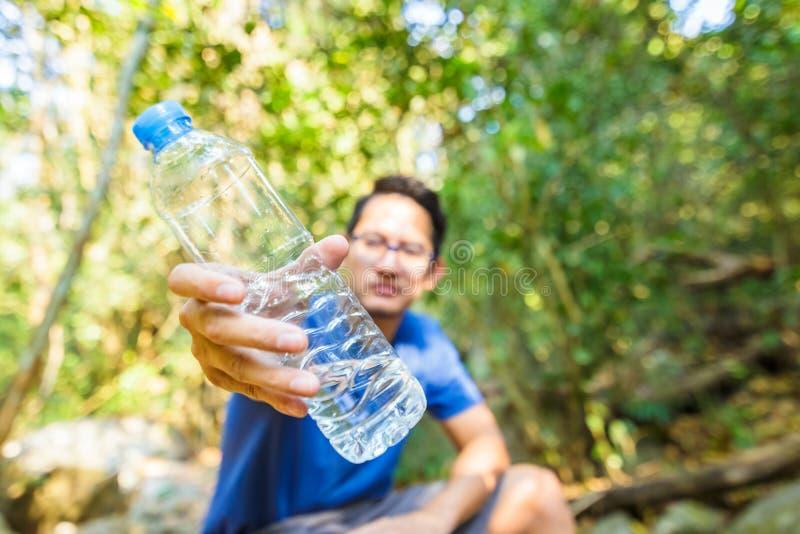 Een mens toont gebotteld drinkwater in het bos stock foto's