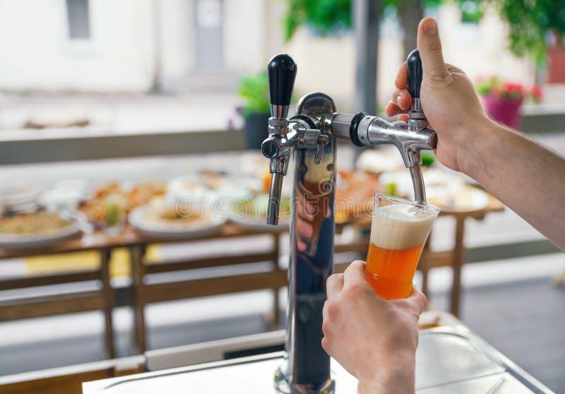 Een mens trekt bier van een kraan in een glas Ontwerpbier De barman giet bier in een glas Bar met bier op het terras van restau stock fotografie