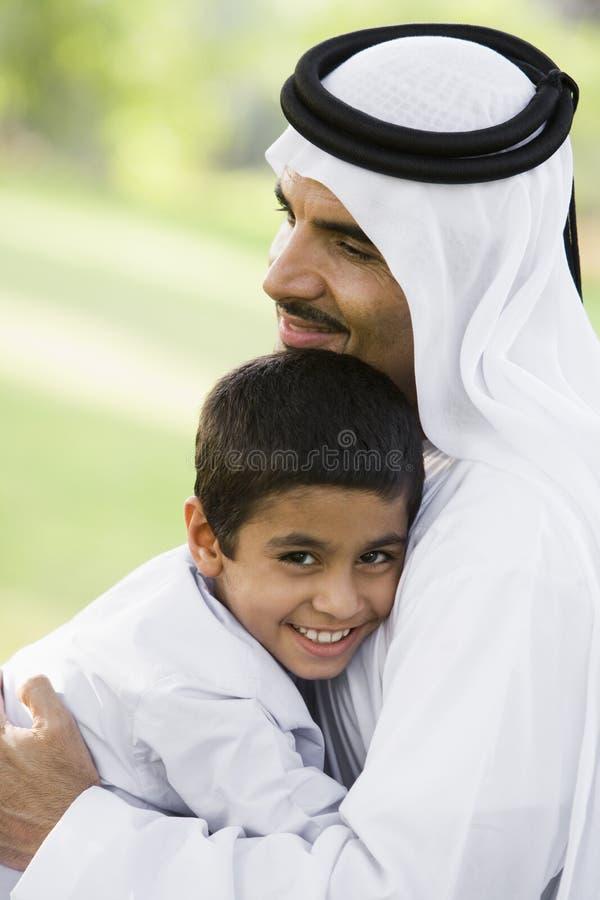 Een mens Van het Middenoosten en zijn zoonszitting in een park royalty-vrije stock fotografie