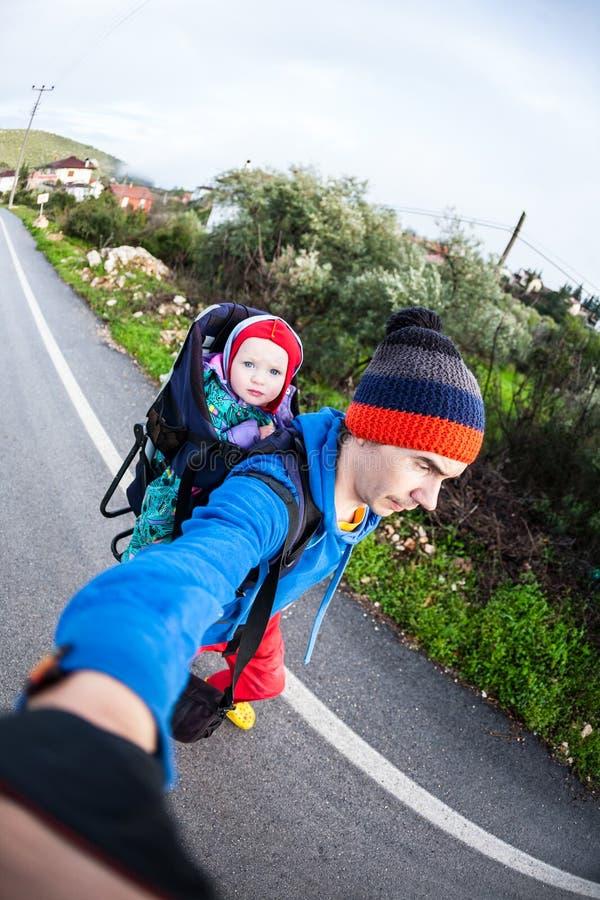 Een mens vervoert een kind in een rugzak stock afbeeldingen