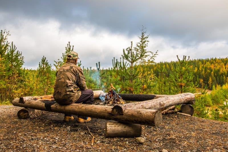 Een mens verwarmt worsten boven het kampvuur in Finland royalty-vrije stock foto's