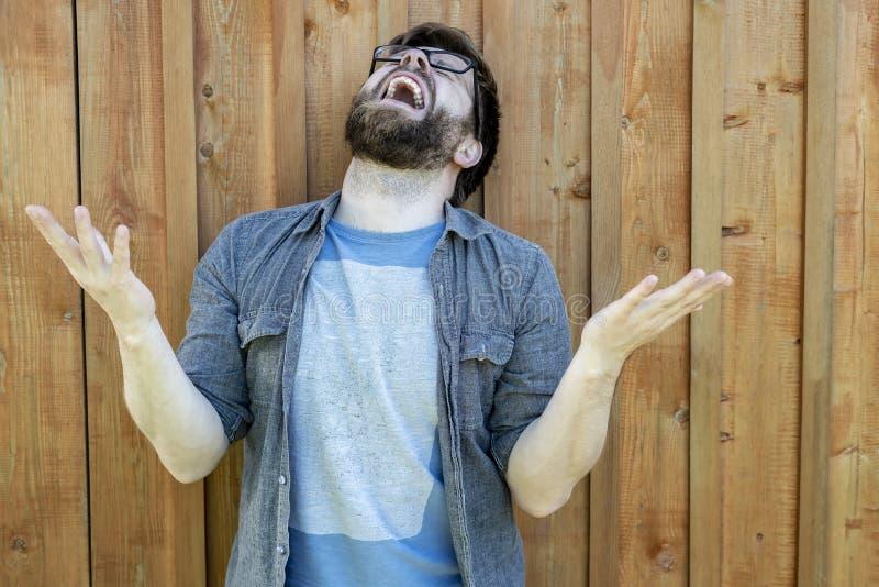 Een mens in wanhoop heft zijn palmen en hoofd op, en schreeuwt luid Uitdrukking van emotieproblemen Geïsoleerd op de achtergrond  royalty-vrije stock fotografie