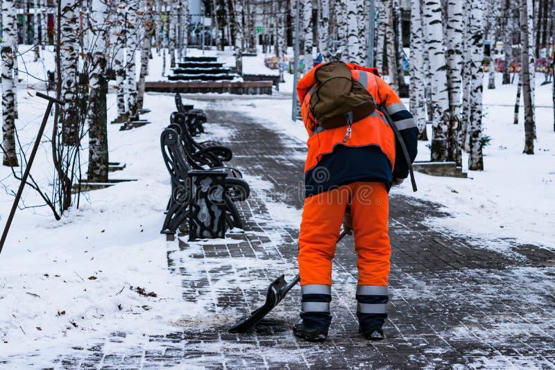 Een mens in werkkledij met een schop verwijdert sneeuw op het spoor in het park in de winter stock foto's